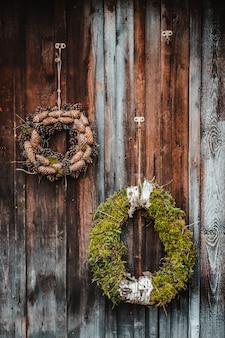 Feestelijke rustieke krans van kegels op een donkere bruine houten achtergrond. het concept van de kerstvakantie en het nieuwe jaar.