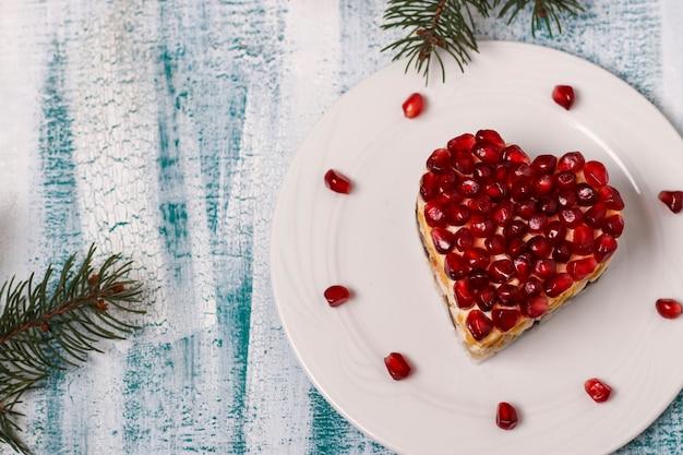 Feestelijke salade in de vorm van een hart, versierd met granaatappelpitjes op een blauwe achtergrond voor valentijnsdag, horizontale oriëntatie, kopie ruimte