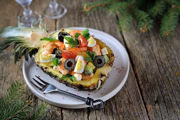 Feestelijke salade van garnalen, kiwi, olijven, zachte kaas, kwarteleitjes, kerstomaatjes in ananasbordjes.