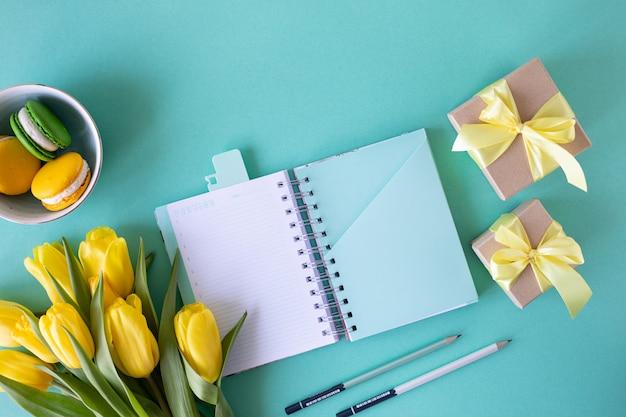 Feestelijke samenstelling: dozen met geschenken, linten, bloemen, sieraden en papieren notitieblok, bovenaanzicht met kopie ruimte