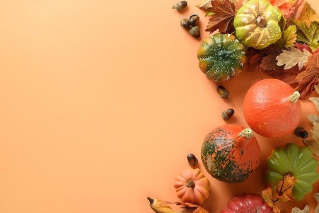 Feestelijke samenstelling van pompoenen, kleurrijke bladeren op een oranje achtergrond met ruimte voor tekst. thanksgiving day en halloween-sjabloon. uitzicht van boven.