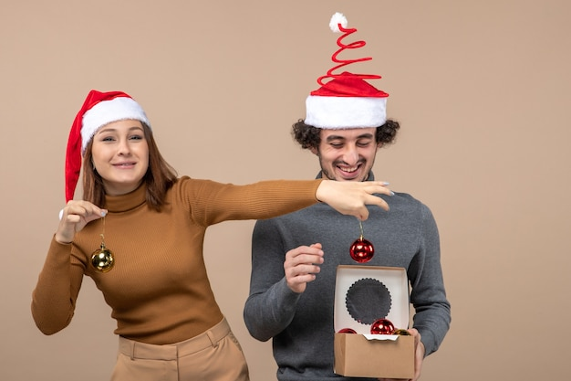 Feestelijke sfeer met opgewonden mooi paar met rode kerstman hoeden decoratie accessoires op grijs openen