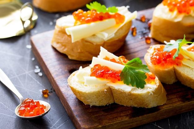 Feestelijke snack sandwiches met rode kaviaar geïsoleerd op een donkere betonnen ondergrond