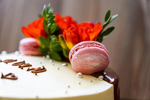 Feestelijke taartdecoratie. kokend biscuitgebak dat met verse bloemen en koekjeskoekjes wordt verfraaid