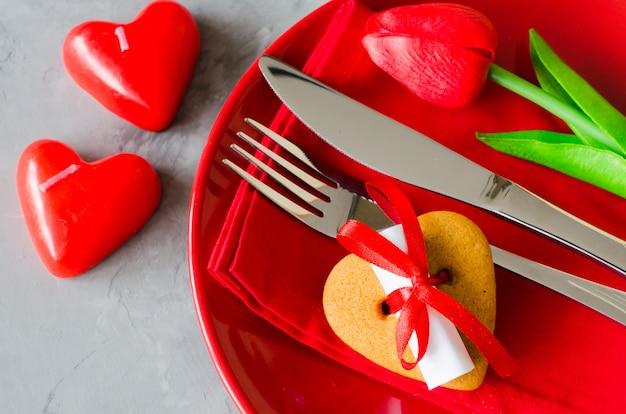 Feestelijke tabel instellen voor valentijnsdag met kaarsen en cookie met een liefdesbrief.