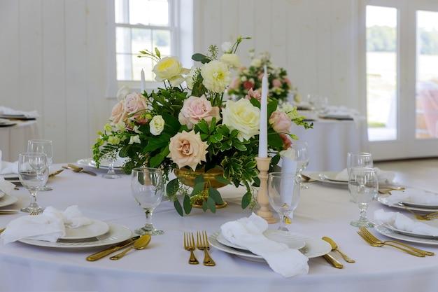 Feestelijke tafel geserveerd voor diner of feest met glazen en bloemen.