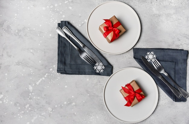 Feestelijke tafel instelling, kerstdiner lunch. witte ambachtelijke plaat, sneeuwvlok decor en cadeau op stenen tafel