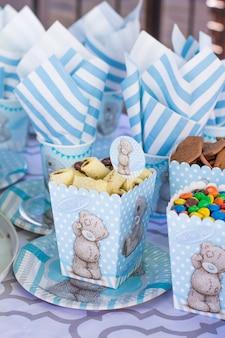 Feestelijke tafel instelling voor kinderen. decoratie voor kinderfeestje. teddybeer stijl serveren. pakketten, koekjes, kopjes, borden en servetten zijn wit-blauw.