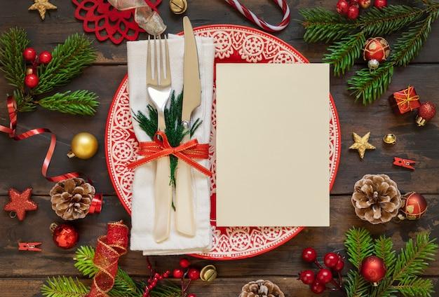 Feestelijke tafel setting met ornamenten sparren takken en blanco kaart bovenaanzicht