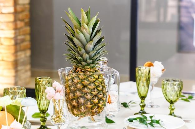 Feestelijke tafel, versierd met vazen, fruit en gebak. in de decoratie van de tafel gebruikte elementen van bloemisterij.