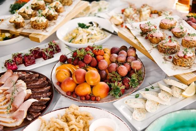 Feestelijke tafel vol heerlijk eten en snacks, mooie opdienen, catering, bruschetta met paté, fruit, vlees