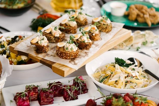 Feestelijke tafel vol met heerlijk eten en hapjes, mooie bediening, catering, bruschetta met paté, fruit