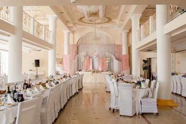 Feestelijke tafel voor de bruid en bruidegom versierd met doek en bloemen
