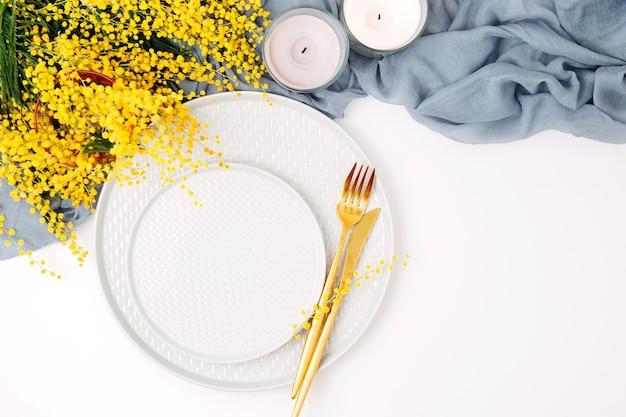 Feestelijke tafelschikking. borden en bestek met grijze decoratieve textiel en gele bloemen op witte achtergrond. mooi platliggend arrangement.