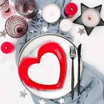 Feestelijke tafelschikking. witte en rode gerechten in de vorm van een hart, drankglazen, kaarsen en bestek witte achtergrond. valentijnsdag of bruiloft concept