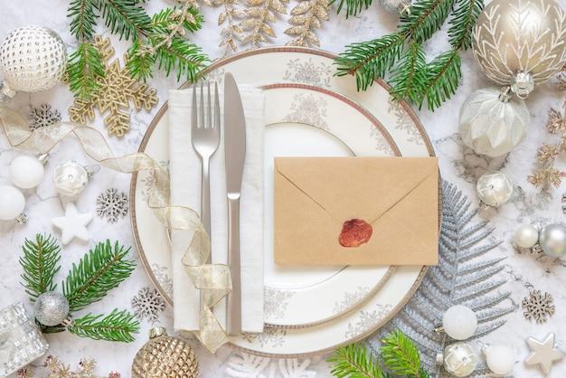 Feestelijke tafelsetting met ornamenten dennentakken en verzegelde envelop bovenaanzicht