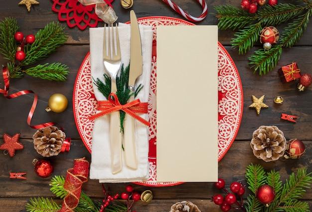Feestelijke tafelsetting met ornamenten en dennentakken en blanco kaartsjabloon