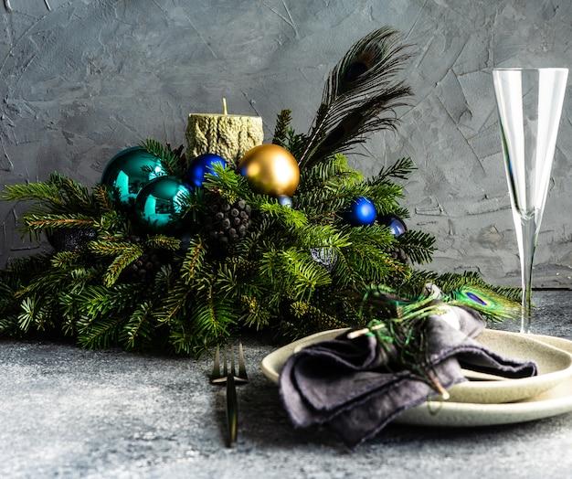 Feestelijke tafelsetting versierd met pauwenveer voor het kerstdiner op stenen bord