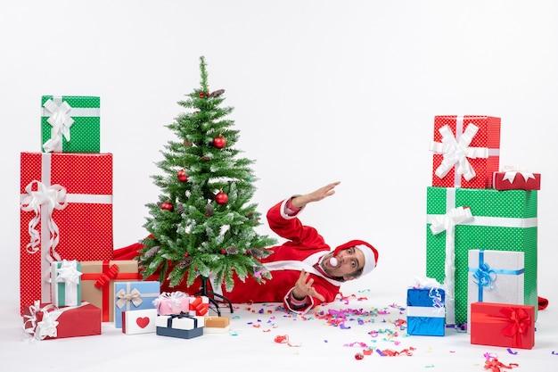 Feestelijke vakantiestemming met de jonge kerstman die achter de kerstboom ligt in de buurt van geschenken op een witte achtergrond