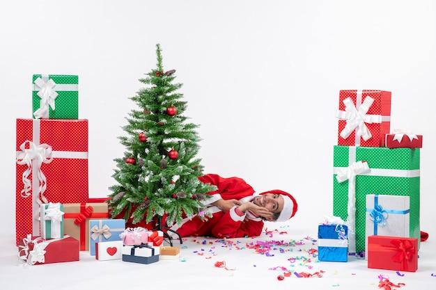 Feestelijke vakantiestemming met de kerstman achter de kerstboom in de buurt van geschenken in verschillende kleuren op witte achtergrond stock foto
