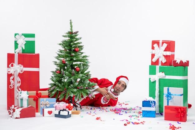 Feestelijke vakantiestemming met de kerstman achter de kerstboom in de buurt van geschenken in verschillende kleuren op witte achtergrond