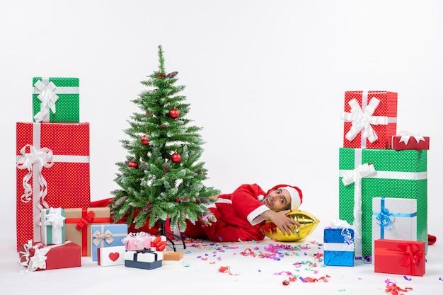 Feestelijke vakantiestemming met de kerstman achter de kerstboom in de buurt van geschenken in verschillende kleuren op witte achtergrondbeelden