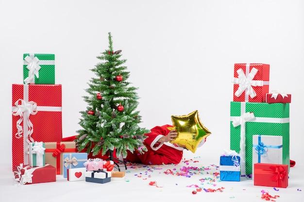 Feestelijke vakantiestemming met de kerstman die achter de kerstboom ligt en zijn gezicht sluit in de buurt van geschenken in verschillende kleuren op witte achtergrond