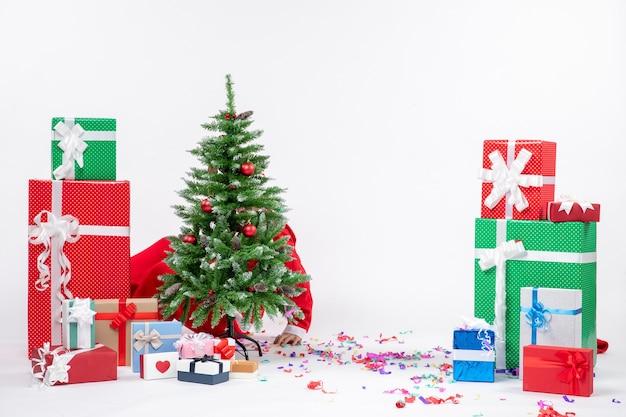 Feestelijke vakantiestemming met de kerstman verstopt achter versierde kerstboom op witte achtergrond