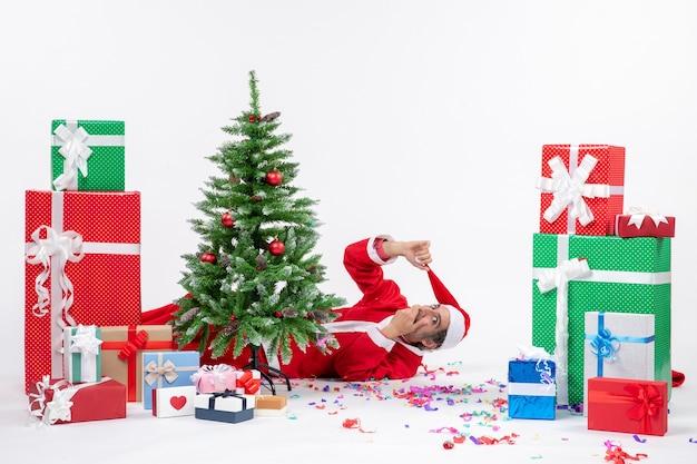 Feestelijke vakantiestemming met jonge verraste kerstman die achter de kerstboom in de buurt van giften op witte achtergrond ligt