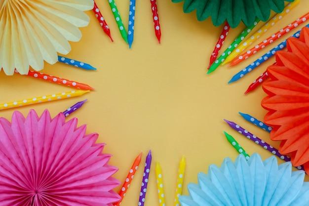 Feestelijke verjaardag kleurrijke kaarsen en papieren fans op pastel gele verjaardag of feest