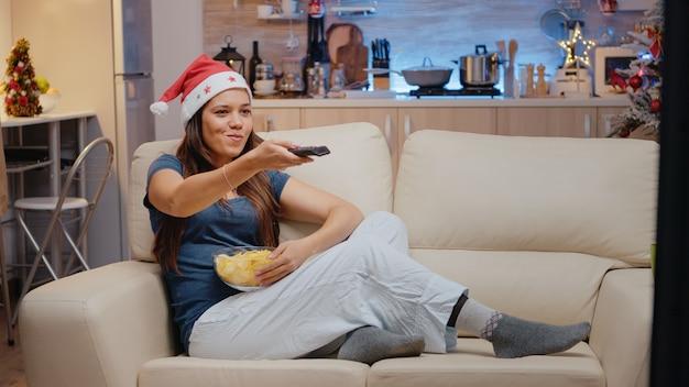 Feestelijke vrouw die een kerstmuts draagt en komedie op tv kijkt