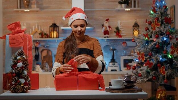 Feestelijke vrouw die geschenken voorbereidt met inpakpapier