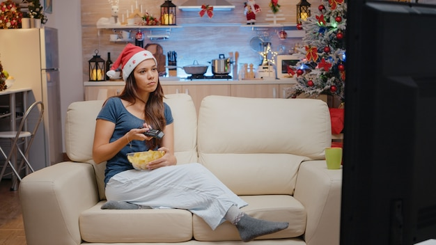 Feestelijke vrouw die televisie kijkt en chips uit een kom eet