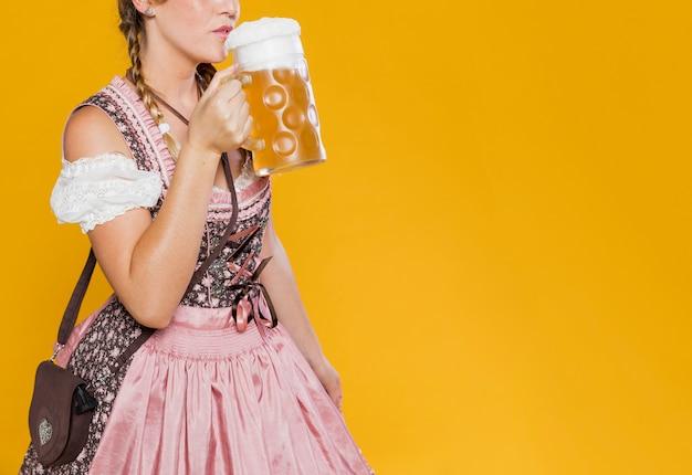 Feestelijke vrouw in kostuum klaar om bier te drinken