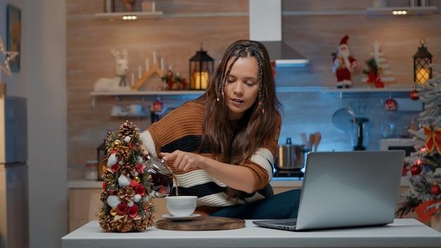 Feestelijke vrouw praten over video-oproep met behulp van laptop