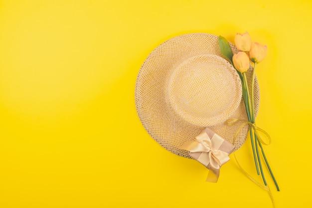 Feestelijke vrouwelijke mode plat lag met kopie ruimte. geschenkdoos, strohoed en gele tulpen