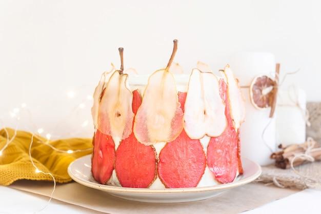 Feestelijke witte cake versierd met rode en witte perenplakken