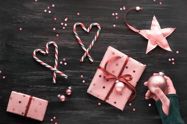 Feestelijke zwart-wit roze kerstmisachtergrond met roze giftdozen, gestreept snoepriet, snuisterijen, sterren en confetti. geometrische creatieve plat lag met kopie-ruimte