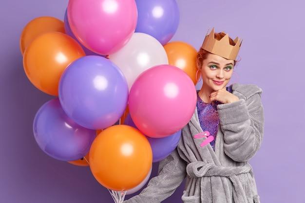 Feestmeisje kijkt zelfverzekerd vooraan geniet verjaardagsviering gekleed in huiselijke outfit houdt opgeblazen kleurrijke ballonnen vormt binnen over paarse muur