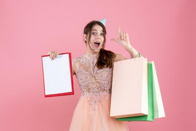 Feestmeisje met feestmuts met documenten en boodschappentassen die met de vinger op roze wijzen