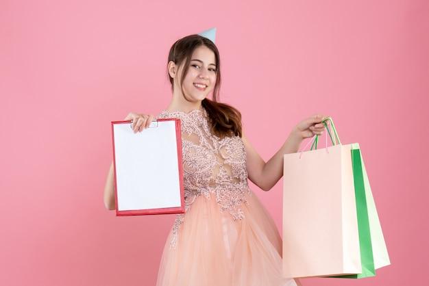 Feestmeisje met feestmuts met documenten en boodschappentassen op roze