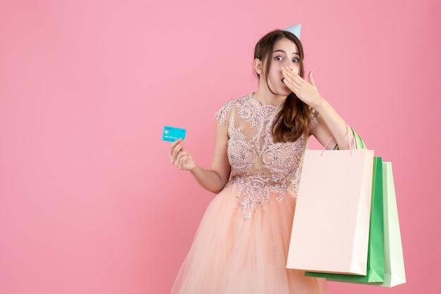 Feestmeisje met feestmuts met kaart en boodschappentassen die hand naar haar mond op roze brengen