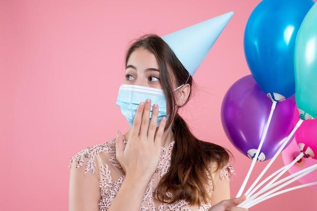 Feestmeisje met kroon en masker met ballonnen op roze