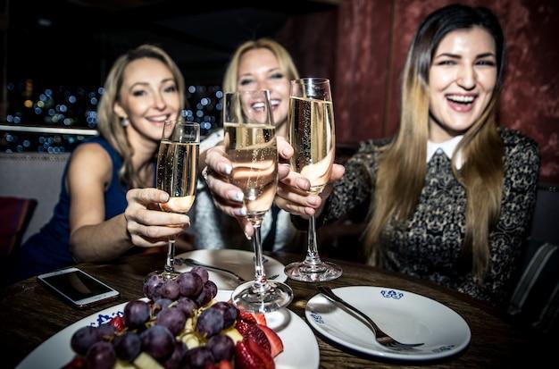 Feestmeisjes in een restaurant vieren met drankjes en champagne