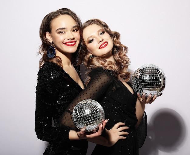 Feestmeisjes in zwarte jurk met discoballen
