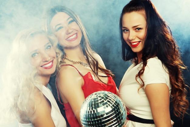 Feestmeisjes met discobal, blij en glimlach.