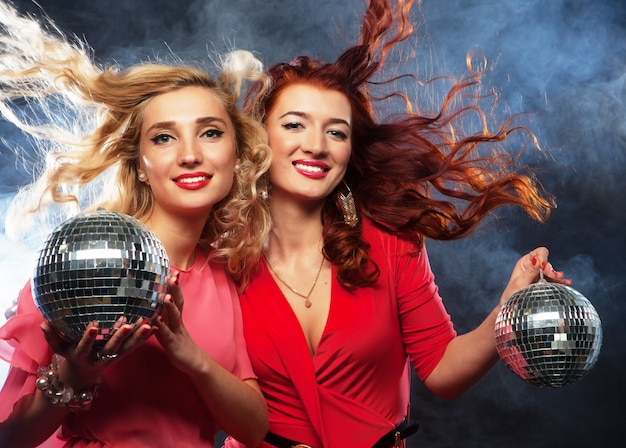 Feestmeisjes met discobal, gelukkig en glimlach