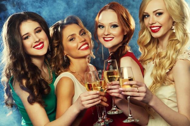 Feestmeisjes rammelende fluiten met mousserende wijn