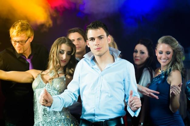 Feestmensen dansen in discoclub