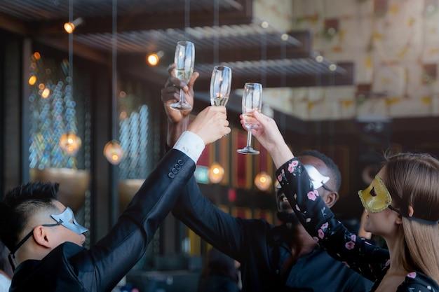 Feestmensen houden van masker van uitvoerend bedrijfsteam dat wijnglas oppakt om te drinken en te praten.